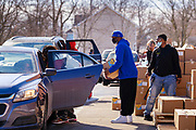 "27 FEBRUARY 2021 - DES MOINES, IOWA: Volunteers load emergency food boxes into a car during a touchless emergency food distribution at the John R. Grubb Community YMCA in Des Moines. The food distribution was organized by Farmers to Families and the YMCA. They had 1,000 boxes of emergency rations which included fresh fruit and vegetables, yogurt, chicken and hot dogs. They also had 1,000 gallons of milk. The neighborhood around the YMCA is a ""food desert,"" with no nearby grocery stores that sell healthy food. Food bank use in Iowa is up more than 60% since the start of the Coronavirus pandemic. Food bank officials estimate that 4 in 10 users are new users of emergency food pantries.        PHOTO BY JACK KURTZ"