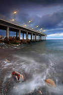 The beach of Pietra Ligure in Liguria, Italy. Taken on a stormy and windy night at the beginning of March, under some pouring rain. There were only two people at the beach that night: the fisherman on the pier and... a photographer!