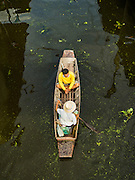 27 SEPTEMBER 2016 - BANGKOK, THAILAND:  A man and his friend in a canoe on the khlong (canal) near the floating market in Damnoen Saduak, Thailand. The market is famous because vendors cruise the canals around the market selling produce and tourist curios. It is one of the best known tourist attractions in Samut Songkhram province.     PHOTO BY JACK KURTZ