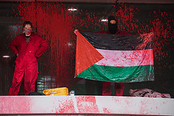 Sandwich, UK. 4th October, 2021. Two Palestine Action activists, one holding a Palestinian flag, occupy an area above the entrance to Discovery Park House after it was sprayed with red paint in protest against the presence in Discovery Park of an Instro Precision factory. Instro Precision is a subsidiary of Elbit Systems, Israel's largest publicly-traded arms company which markets drones used extensively by the Israeli military in Gaza as 'battle-proven', and it supplies 'high precision military equipment'. Palestine Action contends that equipment sold by Instro Precision has been used by the Israeli military against the civilian population of Gaza.