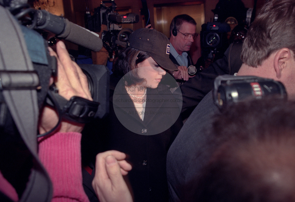 Former White House intern Monica Lewinsky is escorted through the lobby of the Mayflower Hotel past waiting press January 23, 1999 after arriving in Washington, DC. Lewinsky was ordered by a Federal judge to submit to an interview sought by House prosecutors in President Clinton's impeachment trial.