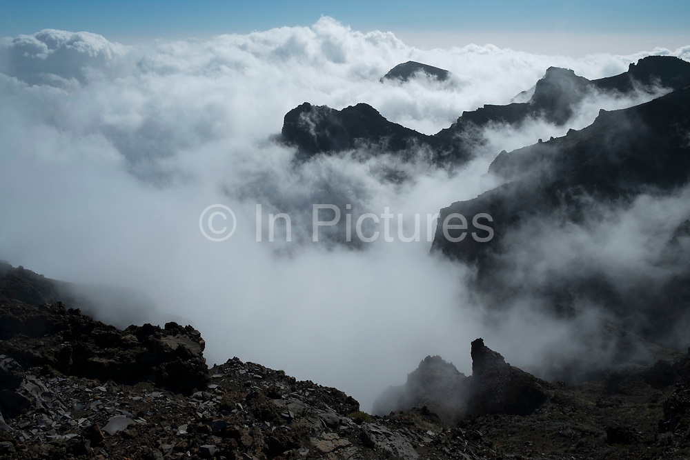 View from the Roque de los Muchachos above the clouds looking south to the Caldera de Taburiente National Park in La Palma, Canary Islands, Spain. La Palma, also San Miguel de La Palma, is the most north-westerly Canary Island in Spain. La Palma has an area of 706km2 making it the fifth largest of the seven main Canary Islands. Caldera de Taburiente National Park Spanish: Parque Nacional de la Caldera de Taburiente is a national park on the island of La Palma, Canary Islands, Spain. It contains the enormous expanse of the Caldera de Taburiente, once believed to be a huge crater, but nowadays known to be a mountain arch with a curious crater shape, which dominates the northern part of the island. It was designated as a national park in 1954. The caldera is about 10km across, and in places the walls tower 2000 m over the caldera floor.