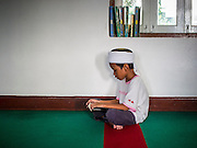 03 JULY 2014 - BANGKOK, THAILAND: A boy reads his Quran at Haroon Mosque in Bangkok during the holy month of Ramadan. Ramadan is the ninth month of the Islamic calendar, and the month in which Muslims believe the Quran was revealed. The month is spent by Muslims fasting during the daylight hours from dawn to sunset. Fasting during the month of Ramadan is one of the Five Pillars of Islam. Muslims believe that the Quran was sent down during this month, thus being prepared for gradual revelation by Jibraeel (Gabriel) to the prophet Muhammad.      PHOTO BY JACK KURTZ