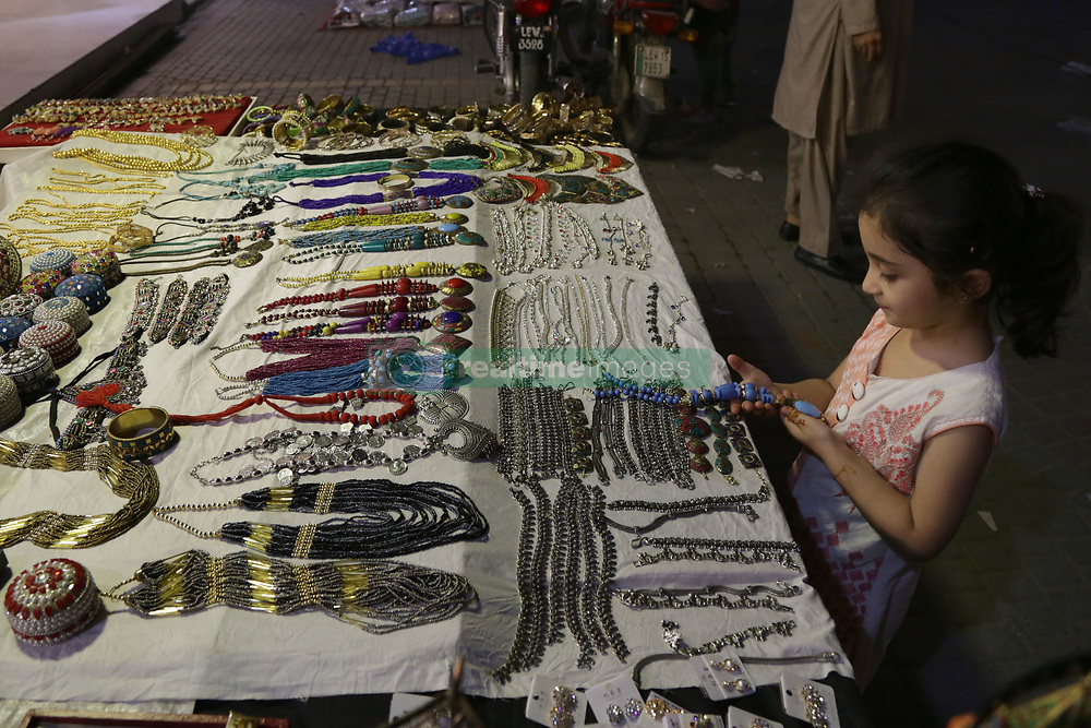 June 14, 2018 - Pakistan - Pakistani people shop at a market ahead of the Muslim festivities of Eid al-Fitr, during the month of Ramadan. Muslims around the world are preparing to celebrate the Eid al-Fitr holiday, which marks the end of the fasting month of Ramadan. (Credit Image: © Rana Sajid Hussain/Pacific Press via ZUMA Wire)