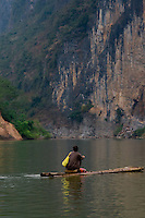A man gliding along the Ming River on a traditional bamboo raft as we make our way upstream towards the ancient Huashan rock paintings.