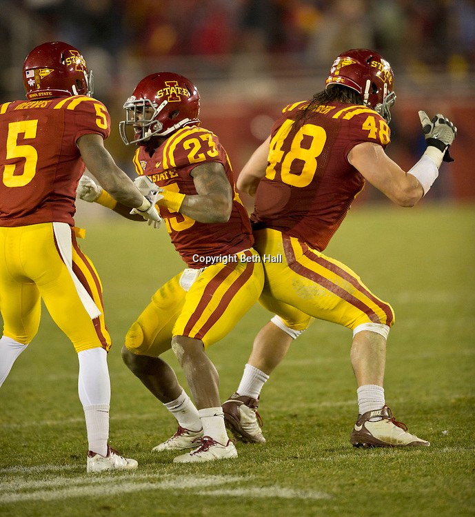Nov 18, 2011; Ames, IA, USA; Iowa State Cyclones defensive back Leonard Johnson (23) and defensive end Jake Lattimer (48) react to a play as defensive back Jeremy Reeves (5) looks on during the second half of a game against the Oklahoma State Cowboys at Jack Trice Stadium. Iowa State Cyclones defeated the Oklahoma State Cowboys 37-31. Mandatory Credit: Beth Hall-US PRESSWIRE Editorial sports photography of the Iowa State Cyclones vs. Oklahoma State Cowboys in 2011 in Aimes, Iowa.