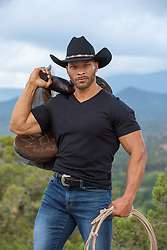 hot muscular black cowboy with a rope and saddle outdoors on a mountain range