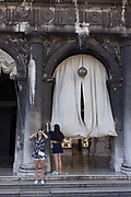 Two Asian girls under the pillars the covered Procuratie Nuovo in Piazza San Marco, Venice, Italy. The Procuratie are three connected buildings on St Mark's Square in Venice. They are historic buildings over arcades, the last of them completed, to finish off the square, under Napoleon's occupation. Venice attracts 22-million visitors each year (for a city of only about 60,000 residents) while the cultural protection organisation, Italian Nostra, warns that Venice can only accommodate about 33,000 visitors per day but currently at least 60,000 daily.