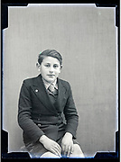 boy posing for a studio portrait circa 1930s