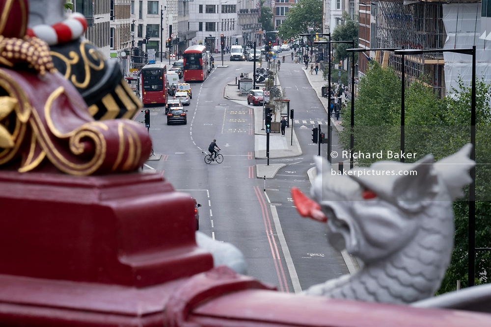 With a flaming tongue of a City Griffin in the foreground, a cyclist crosses traffic and turns across the Farringdon Road in the City of London, the capital's financial district, on 24th June 2021, in London, England. CREDIT RICHARD BAKER.