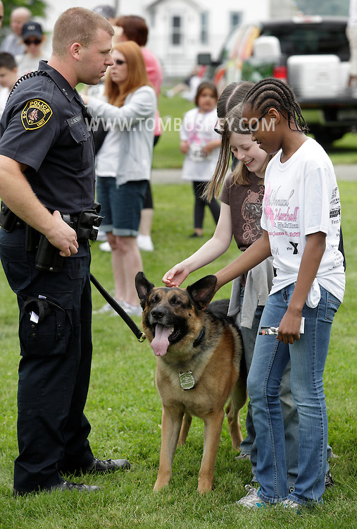 Middletown, New York - Two girls pet police dog Kilo at the festival following the 15th annual Ruthie Dino Marshall 5K Run and Fun Walk hosted by the Middletown YMCA on Sunday, June 5, 2011.
