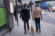 Two men and their little dogs in Shoreditch, East London, UK. It is almost as if each man's dog is part of their overall fashion look. Brown and black dogs to match their outfits. In Shoreditch and Hoxton in London, this would not surprise anyone.