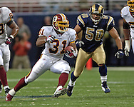 Washington Redskins running back Rock Cartwright (L) rushes up field for 25-yards, past St. Louis Rams linebacker Pisa Tinoisamoa (R) in the second quarter, during the Redskins 24-9 win at the Edward Jones Dome in St. Louis, Missouri, December 4, 2005.