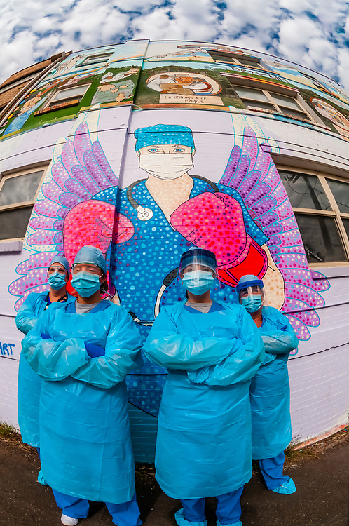 Emergency room nurses wearing Personal Protective Equipment used while fighting the Coronavirus (COVID-19) pandemic, with mural by artist Austin Zucchini-Fowler, Denver, Colorado USA.