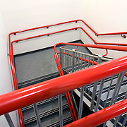 bright red handrail on office emergency exit stairs