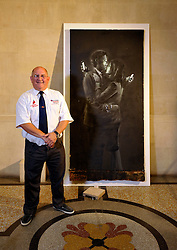 © Licensed to London News Pictures. 27/08/2014; Bristol, UK.  Dennis Stinchcombe MBE of Broad Plain Working with Young People club with The Banksy piece 'Mobile Lovers' which has been sold for £403,000 by Mary McCarthy of MM Contemporary Arts to a private buyer on behalf of the club.  The artwork was placed near to the Riverside Project at the Broad Plain club run by Dennis Stinchcombe MBE.  There was a dispute between Denis and the Mayor of Bristol George Ferguson over the ownership of the artwork which was resolved when Banksy sent a letter to the club saying the artwork was theirs to do with what they wished.  The money from the sale will help fund the continuing activities of the club.<br /> Photo credit: Simon Chapman/LNP
