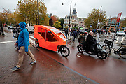 In Amsterdam rijdt een overdekte fietstaxi over het fietspad door de regen.<br /> <br /> In Amsterdam a bicycle cab with cover rides at the bike lane in the rain.