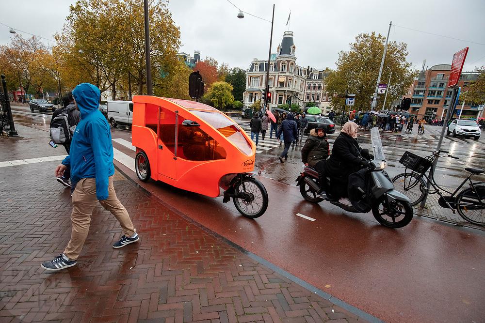 In Amsterdam rijdt een overdekte fietstaxi over het fietspad door de regen.<br /> <br /> In Amsterdam a bicycle cab with cover rides at the bike lane in the rain.