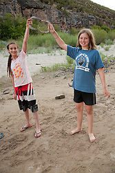 North America, United States, Colorado, Dinosaur National Monument, Green River (Gates of Ladore section), girls holding horseshoes on beach.  MR