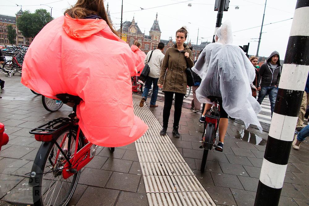 In Amsterdam fietsen toeristen over het voetpad met een huurfiets.<br /> <br /> In Amsterdam tourists ride with the bikes at the pavement.