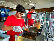 "26 JUNE 2020 - DES MOINES, IOWA: ETHAN KEOMALA makes deep fried Oreos while DRAKE HANSON make mini donuts at Fair Food Friday in Des Moines. The 2020 Iowa State Fair, like many state fairs in the Midwest, has been cancelled this year because of the COVID-19 (Coronavirus) pandemic. The cancellation of the fair left many small vendors stranded with no income. Some of the fair food vendors in Iowa started ""Fair Food Fridays"" on a property a few miles south of the State Fairgrounds. People drive up and don't leave their cars while vendors bring them the usual midway fare; corndogs, fried tenderloin sandwiches, turkey legs, deep fried Oreos, lemonaide and smoothies. Fair Food Friday has been very successful. The vendors serve 450-500 people per Friday and during the lunch rush people wait in line in their cars 30 - 45 minutes to place an order.     PHOTO BY JACK KURTZ"