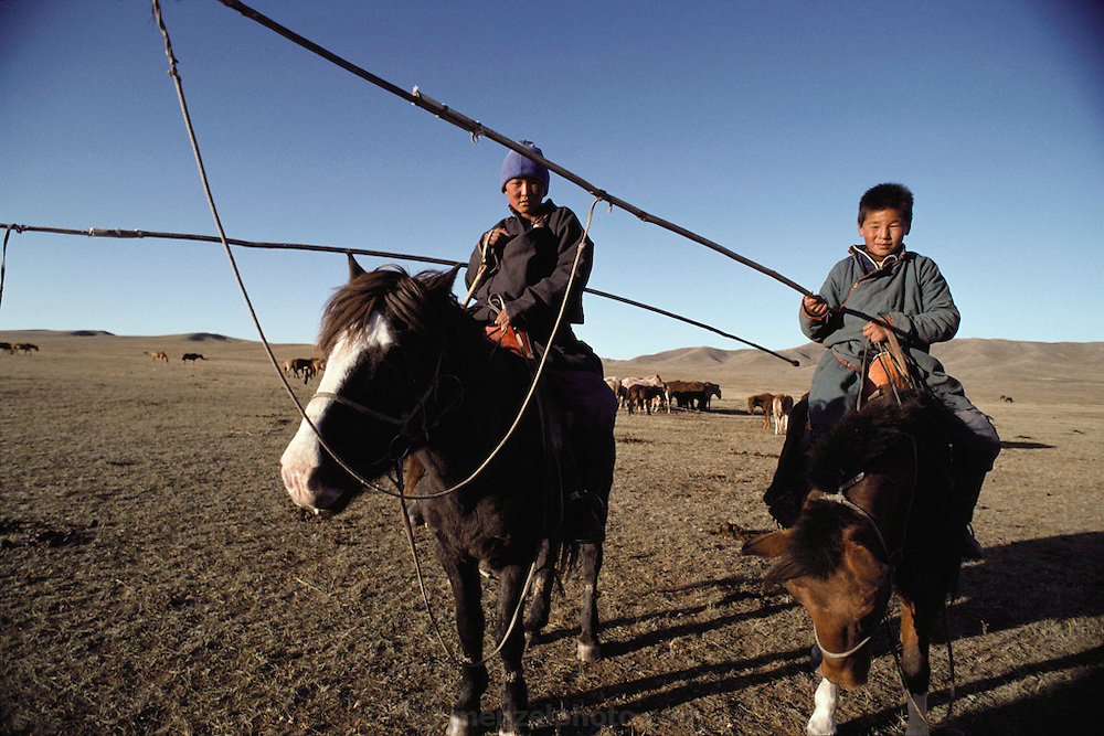 Rural life 35km from Ulaanbaatar, Mongolia. The herding family lives in traditional ger (round tent built from canvas, strong poles, and wool felt). Here two of the sons take a break from lassoing cattle with long poles and rope. Material World Project.