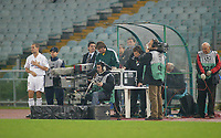 Real Madrid's Michael Owen waits patiently on the touchline, next to TV cameras and soundmen, to come onto the field as a substitute in an empty Stadio Olympico. Fans were banned after the referee was hit by a missle during a previous Champion's League match.