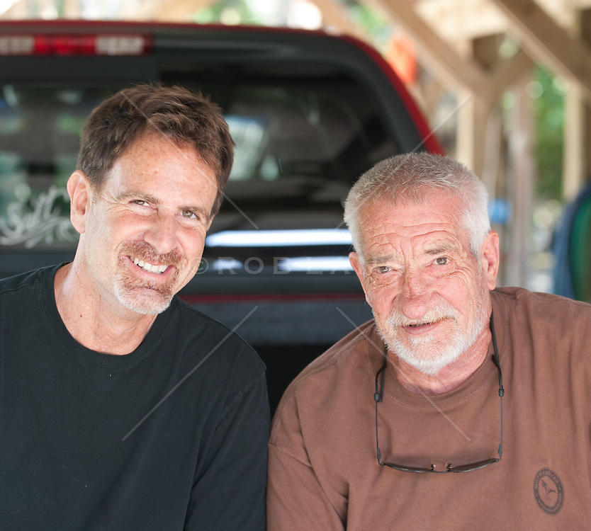 Two Men smiling while seated on the back of a parked truck