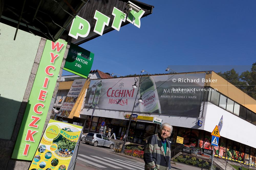 An elderly Polish shopper walks past advertising signs, on 21st September 2019, in Szczawnica, Malopolska, Poland.