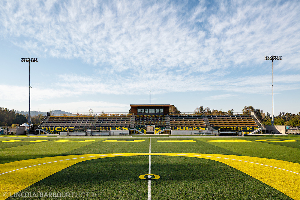 Architectural photo of University of Oregon's Women's Soccer & Lacrosse Stadium. Designed by DLR Group. A view of the bleachers from centerfield. The 'O' in the middle of the field fills the front half of the image. Blue skies overhead.