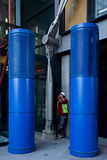 A workmen smokes a cigarette beneath blue theme coloured pillars and struts on the office and housing development opposite the Tate Modern gallery on London's Southbank. The tall pillars may be part of a ventilation facility or simply an aesthetic for the building but also provides a quiet corner for the worker who takes a few minutes away from a nearby construction site. He looks small compared to the high columns and made to look tiny against the large struts that hold the building together.