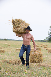shirtless muscular cowboy with hay bales on a ranch