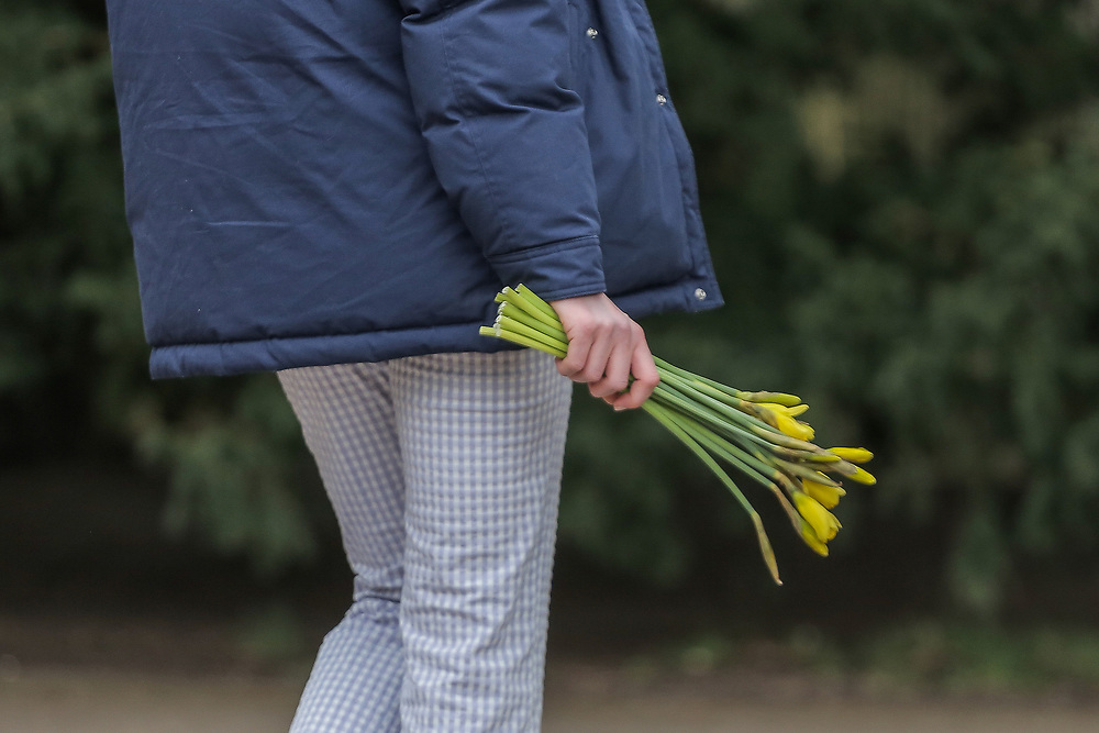 13th, March, 2021. Cheltenham, England. A member of the public holds a set of flowers in memory of Sarah Everard.