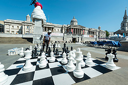 © Licensed to London News Pictures. 18/07/2021. LONDON, UK. A man plays chess on an outdoor chessboard at Chess Fest in Trafalgar Square.  The event celebrates the game of chess and visitors can learn the game, play chess or challenge a Grandmaster.  Also, to celebrate the 150th anniversary of Lewis Carroll's Alice Through the Looking Glass book which featured the game of the chess, 32 actors dressed as Alice Through the Looking Glass characters stand on a giant chessboard replaying a game based on the book.  Photo credit: Stephen Chung/LNP