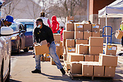 """27 FEBRUARY 2021 - DES MOINES, IOWA: Volunteers load emergency food boxes into a car during a touchless emergency food distribution at the John R. Grubb Community YMCA in Des Moines. The food distribution was organized by Farmers to Families and the YMCA. They had 1,000 boxes of emergency rations which included fresh fruit and vegetables, yogurt, chicken and hot dogs. They also had 1,000 gallons of milk. The neighborhood around the YMCA is a """"food desert,"""" with no nearby grocery stores that sell healthy food. Food bank use in Iowa is up more than 60% since the start of the Coronavirus pandemic. Food bank officials estimate that 4 in 10 users are new users of emergency food pantries.        PHOTO BY JACK KURTZ"""