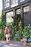 Shopper passes traditional florist shop in the Nine Streets - De Negen Straatjes - 9 Streets district of Jordaan, Amsterdam