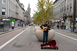 View of musician busking on pedestrianised Union Street in Aberdeen city centre, Scotland, UK