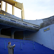 A lady take photographs as a tour group surveys the famous Boca Juniors football stadium, La Bombonera, in La Boca region of Buenos Aires, Argentina, 25th June 2010. Photo Tim Clayton...