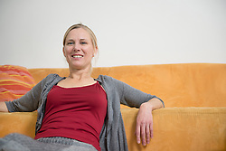 Portrait of mature woman sitting in couch, smiling