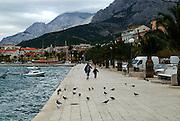 Mother and daughter walking along waterfront, Makarska, Croatia