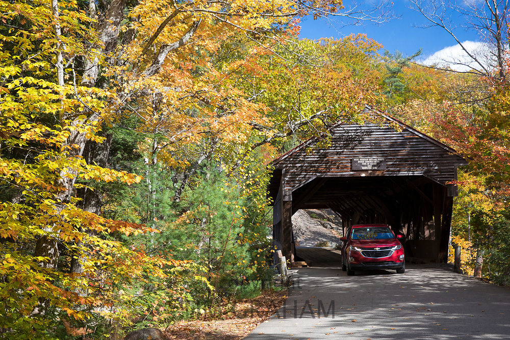 Auto driving through covered bridge along the Kancamagus Highway and Fall foliage in The White Mountains, New Hampshire, USA