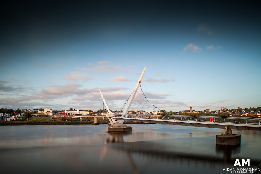 Building Name:PEACE BRIDGE<br /> Building Type: TRANSPORT AND INFRASTRUCTURE - BRIDGE<br /> Architect: WILKINSON EYRE ARCHITECTS<br /> Architect Website: www.wilkinsoneyre.com<br /> Town:DERRY<br /> Year of Completion: 2011<br /> County:DERRY/LONDONDERRY<br /> Collection: Architecture<br /> Country: United Kingdom<br /> After winning a contractor-led design competition, Wilkinson Eyre Architects was commissioned to design a 235m long cycle/footbridge across the River Foyle in Derry~Londonderry. Linking former army barracks with the historic city centre across the water, the bridge has an S-shaped alignment which resolves two skewed axes at each abutment and responds to views up and down the river. Funded by EU PEACE III monies, the bridge is conceived as a pair of self-anchored suspension bridges which overlap visually and structurally at the middle of the river in a symbolic demonstration of unity and concord. An array of filigree hangers support one edge of the bridge deck from catenary cables which are themselves supported at high level from raking masts. The fluid lines of the composition frame views of the historic city and provide a contextual landmark for future generations.<br /> Suspension Bridges, Peace Bridge Derry, Peace Bridge Lonodonderry, Peace bridge Image Series, Transport Structure, Architectural photography, Transport Structures, Architecture photography, River Foyle, Bridge, Bridges, Eu Peace III, Europe Landmark, Riverbank, S Shape, Walking, Derry City, Walkway, Cityscape, Londonderry, Civil Engineering, Footbridge, Wilkinson Eyre Architects, Cycle Bridge.