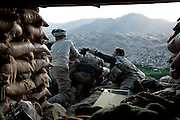 Specialist David Burdette and PFC Caven Cox react to sniper fire at a mountain-top observation post.