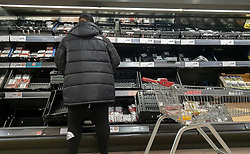 © Licensed to London News Pictures. 11/10/2021. London, UK. A shopper looks at nearly empty shelves of fruit and vegetables in Sainsbury's, north London. This is amid fears of food shortages leading up to Christmas, due to labour shortages, following Brexit. Leading supermarkets may start rationing certain items ahead of Christmas. Photo credit: Dinendra Haria/LNP
