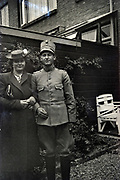 Dutch army police posing with a girl in the backyard of a row house 1950s Netherlands