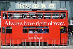 Detail of red Hong Kong tram outside headquarter building of HSBC bank in Hong Kong