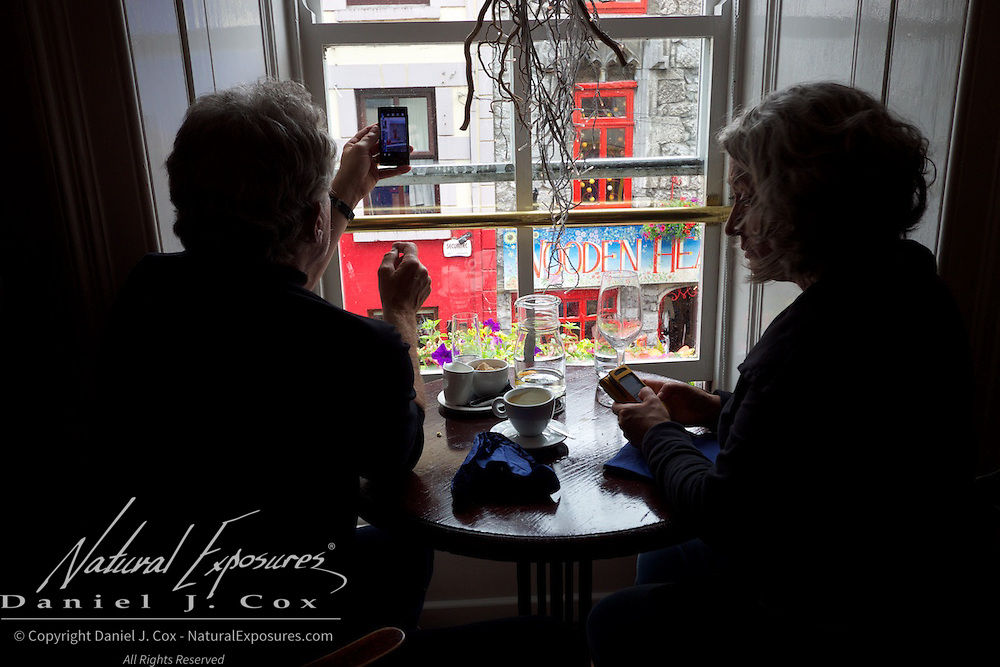 A gentleman shoots photos with a camera phone out a window on to the streets of Galway, Ireland.