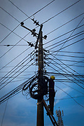 A workman stands at the top of a ladder fixing electricity cables to a pylon on the street in Tejgaon railway district of Dhaka on the 25th of September 2018 in Dhaka, Bangladesh. (photo by Andrew Aitchison / In pictures via Getty Images)