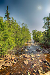 The river runs through the forest of green trees and pours over the large rocks into Lake Superior
