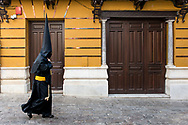 """A penitent walks in a street of Seville. On the building writing in Latin go: """"Hail Mary, full of grace, the Lord is with thee"""". Andalusia, Spain"""